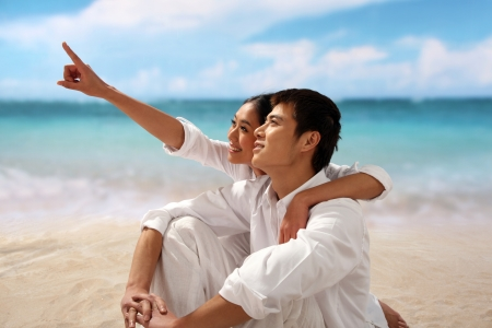 Young couple sitting at beach,embracing photo