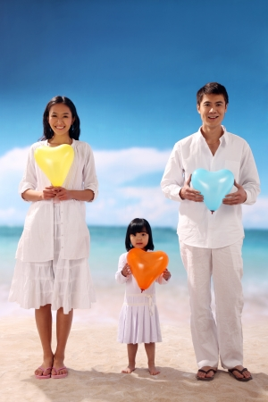 Family of three holding heart shape balloon at beach photo