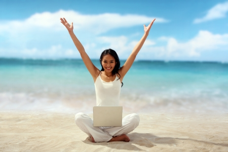 Woman sitting at beach with laptop on her legs photo