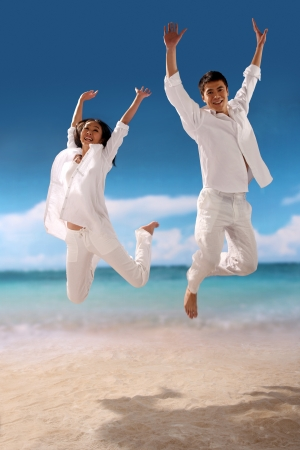 Couple jumping for joy at the beach photo