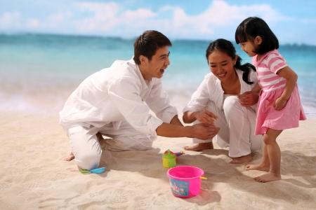 Family of three playing at beach photo
