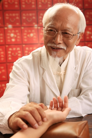 Chinese traditional herbalist doctor taking patients pulse