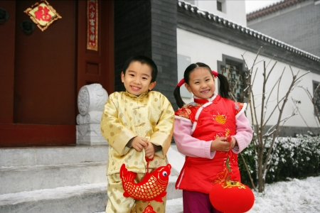 Two children(5-15 years) standing in front of chinese traditional house door smiling Stock Photo - 23325433