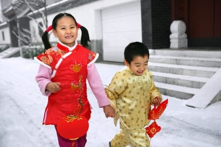 Two children(5-7 years) walking in front of chinese traditional houses smiling Stock Photo - 23325435
