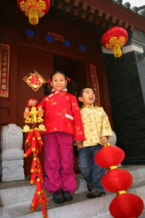 Two children(5-39 years) standing in front of chinese traditional house door smiling Stock Photo - 23325436