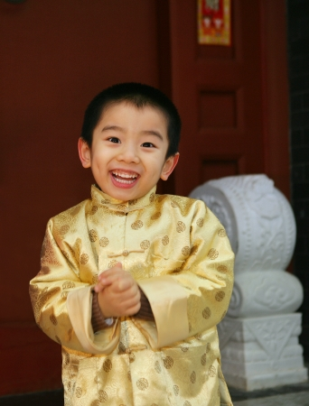 One chinese boy(4-5 years) standing in a Chinese traditional house gate smiling Stock Photo - 23325439