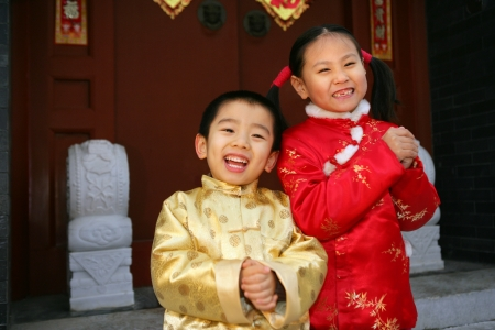 Two children(5-38 years) standing in front of chinese traditional house door smiling Stock Photo - 23325440