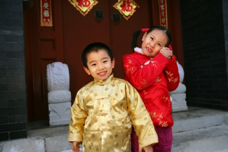 Two children(5-37 years) standing in front of chinese traditional house door smiling Stock Photo - 23325441