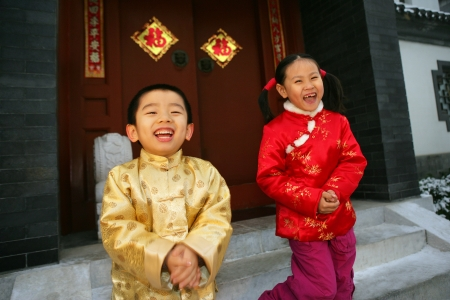 Two children(5-36 years) standing in front of chinese traditional house door smiling Stock Photo - 23325443