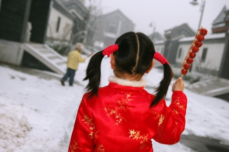 sugarcoated: back view of two chinese children holding sugar-coated haws standing in front of a traditonal house Stock Photo