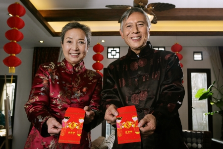 Chinese mature couple making a wish with a red packet photo