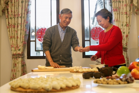 Chinese mature couple making chinese dumpling on New year's Eve photo
