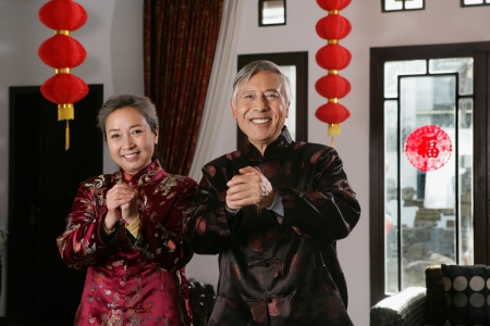 Chinese mature couple making a wish with hands clasped Stock Photo - 23325635
