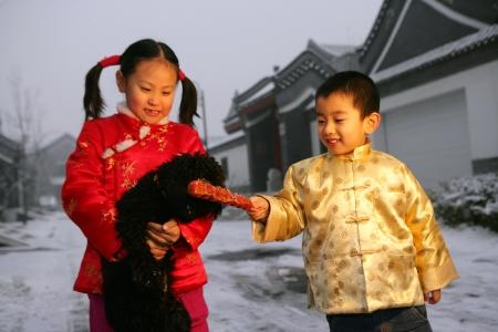 niños chinos: dos niños chinos jugando con un perro negro en la nieve