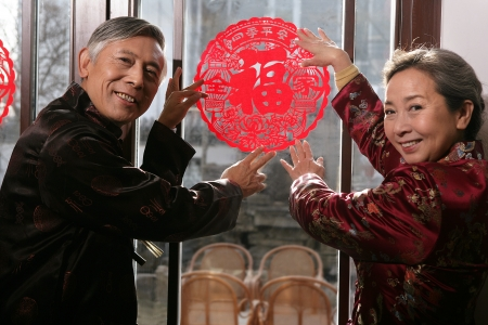 Chinese mature couple holding chinese cut paper on New year's Eve Stock Photo - 23325845