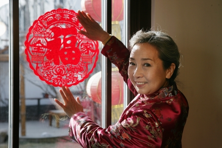 Chinese mature women posting a chinese cut paper on window Stock Photo - 23325880
