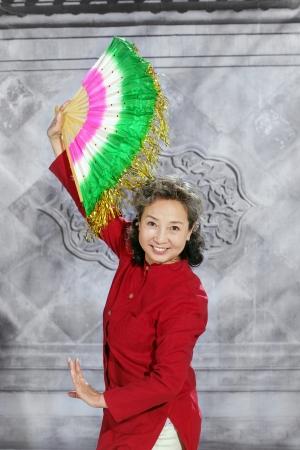 oriental senior woman dancing with fan photo