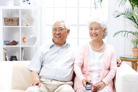 pareja viendo tv: Un tiro de la antigua pareja viendo la televisi�n en casa