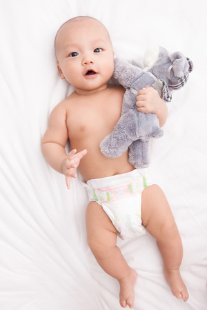 naivete: A shot of baby lying on bed  Stock Photo