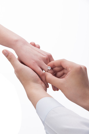 A shot of Man wearing ring to woman photo