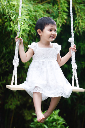 A shot of Girl sitting on swing photo