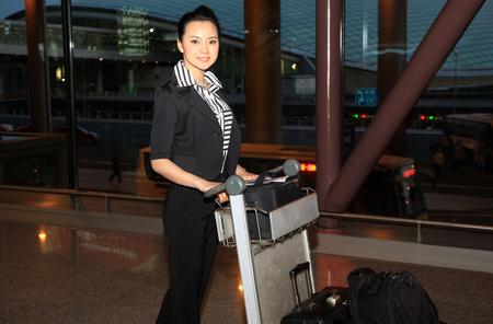 A shot of Business woman pushing luggage cart