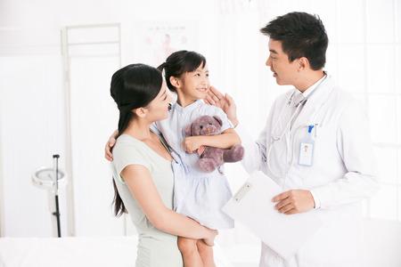 Médico y una niña con su madre Foto de archivo - 30133125