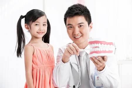 doctor teaching the girl brush teeth photo