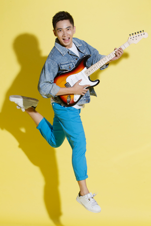 oriental ethnicity: Young man playing guitar Stock Photo