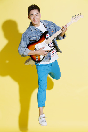 fender stratocaster: Young man playing guitar Stock Photo