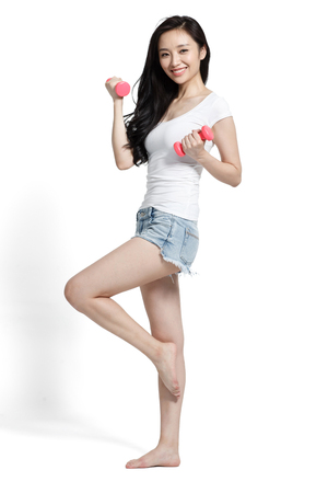 oriental ethnicity: The young woman holding a dumbbell exercise Stock Photo