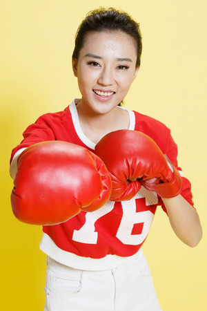 oriental ethnicity: Young women wear boxing gloves Stock Photo