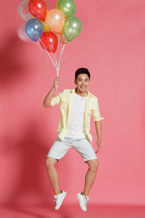 moving activity: A young man holding a balloon Stock Photo