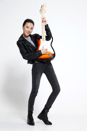 oriental ethnicity: Young woman playing guitar