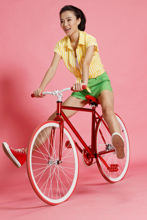east riding: Young woman riding a bicycle