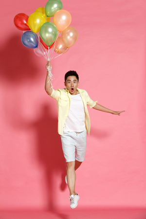 full shot: A young man holding a balloon Stock Photo