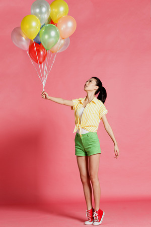 oriental ethnicity: A young woman holding a balloon