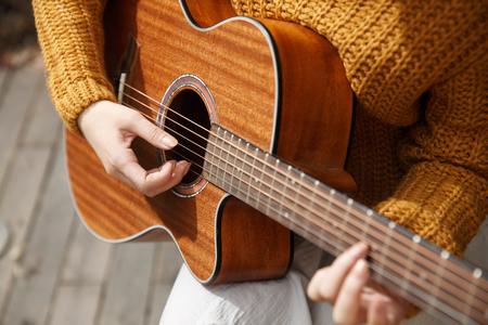 plucking: Young woman playing guitar