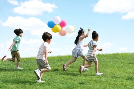 幸せな子供たちは草の上で遊んでいた 写真素材