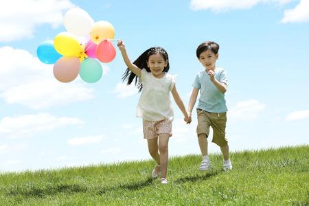 幸せな子供たちは草の上で遊ぶ