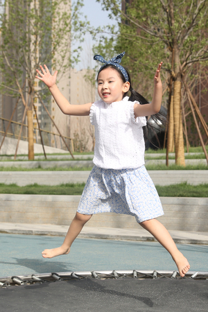 The little girl plays trampoline