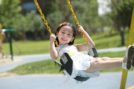 The little girl swings on the swings