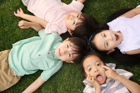 The happy children were playing on the grass Stock Photo