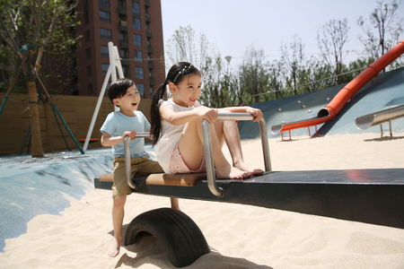 Happy children play on the seesaw
