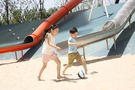 Children are kicking football in the sand Stock Photo