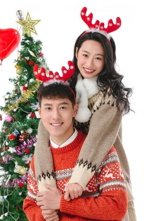 Happy young couple in winter attire celebrating Christmas