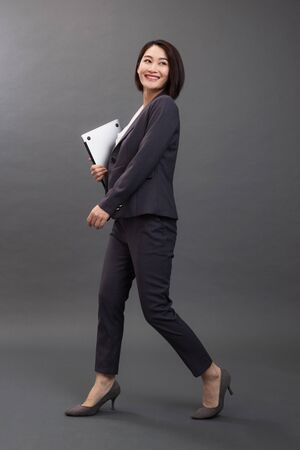 Happy young woman holding laptop
