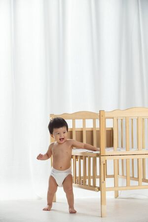 Lovely baby with wooden bed
