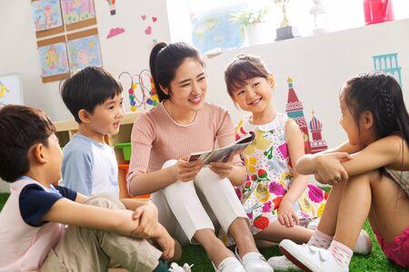 Kindergarten teacher tells the children stories Stock fotó