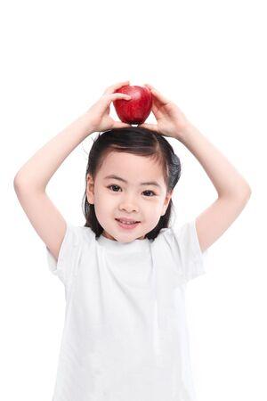 Cute little girl holding an apple on her head 版權商用圖片